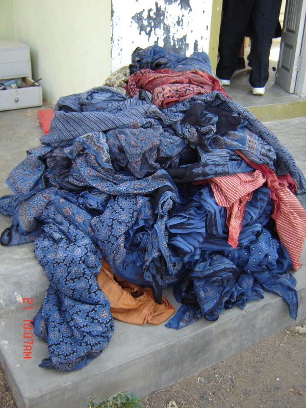 Indigo Dyed Textiles, Bhuj, Gujarat, India. Pile of dyed Indigo textiles on an Indian doorstep waiting for a camel car to take them to market. Photo from Penny Peter's 2007 trip to India.