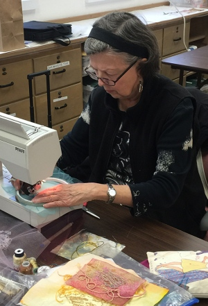Gloria Shelton stitching metal threads on a sheer that can be burnt away.